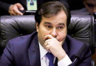 Rodrigo Maia, deputado pelo DEM-RJ. Ele está usando terno escuro, sentando na mesa da presidênci da Câmara do Deputados com um semblante preocupado.